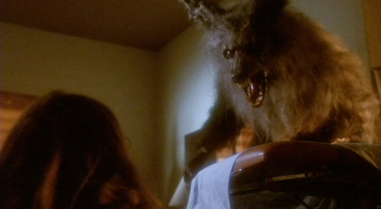 Image is from the film 'The Howling' (1981). A werewolf in wolf form looms over a casket and bares its teeth at a young woman.